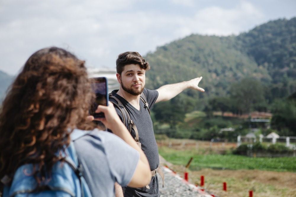 Female taking photo of traveler pointing at green hill in countryside