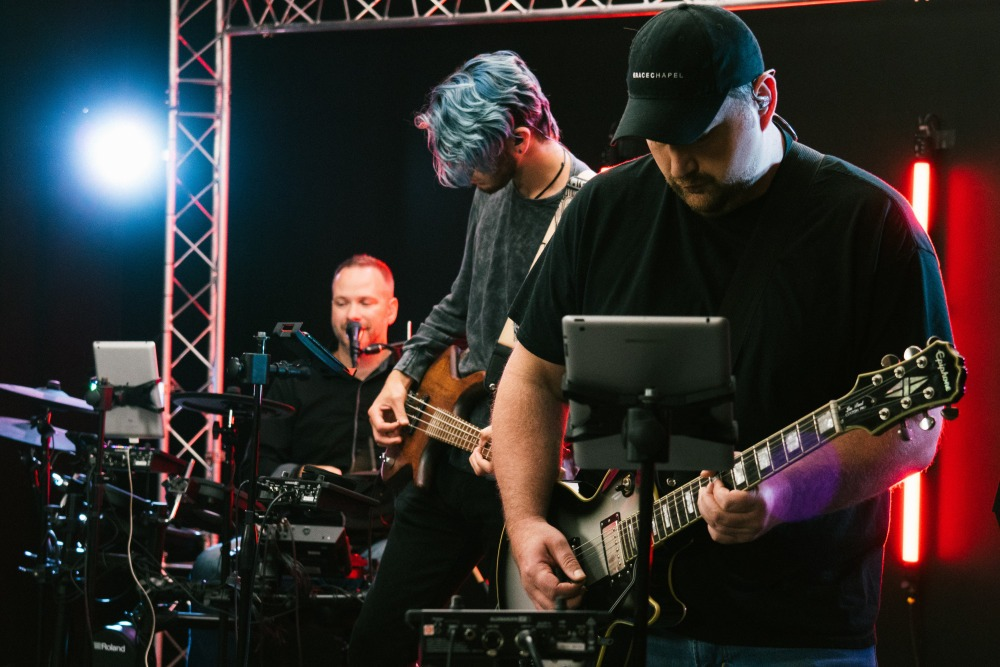 man in black crew neck t-shirt playing guitar