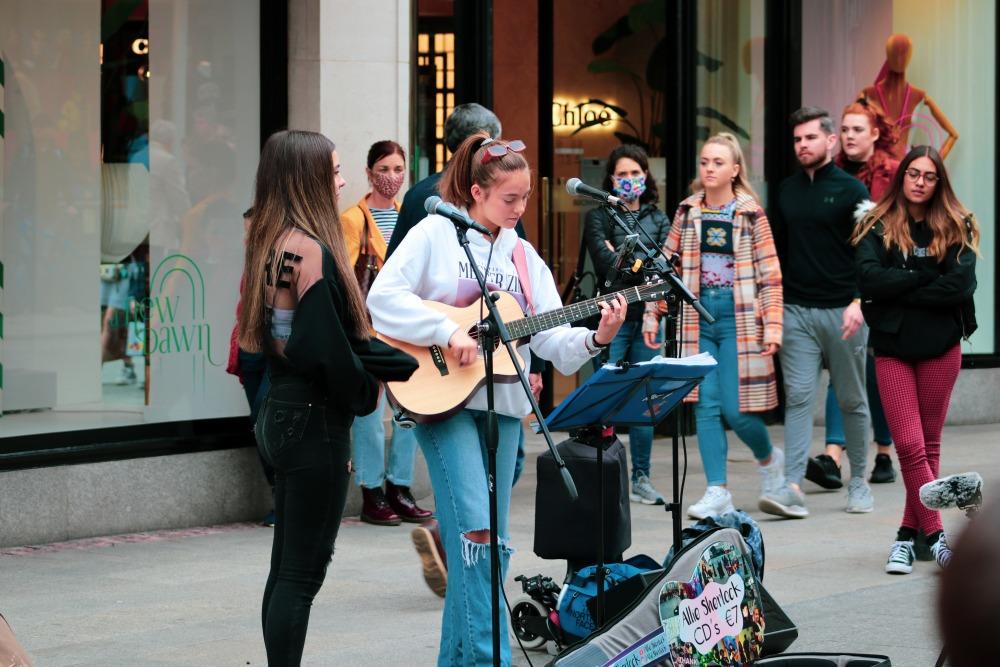 man in black suit playing guitar beside woman in black long sleeve shirt
