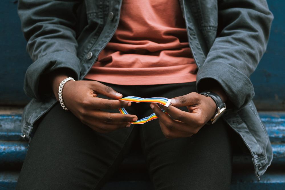 Crop unrecognizable black man holding rainbow bracelet