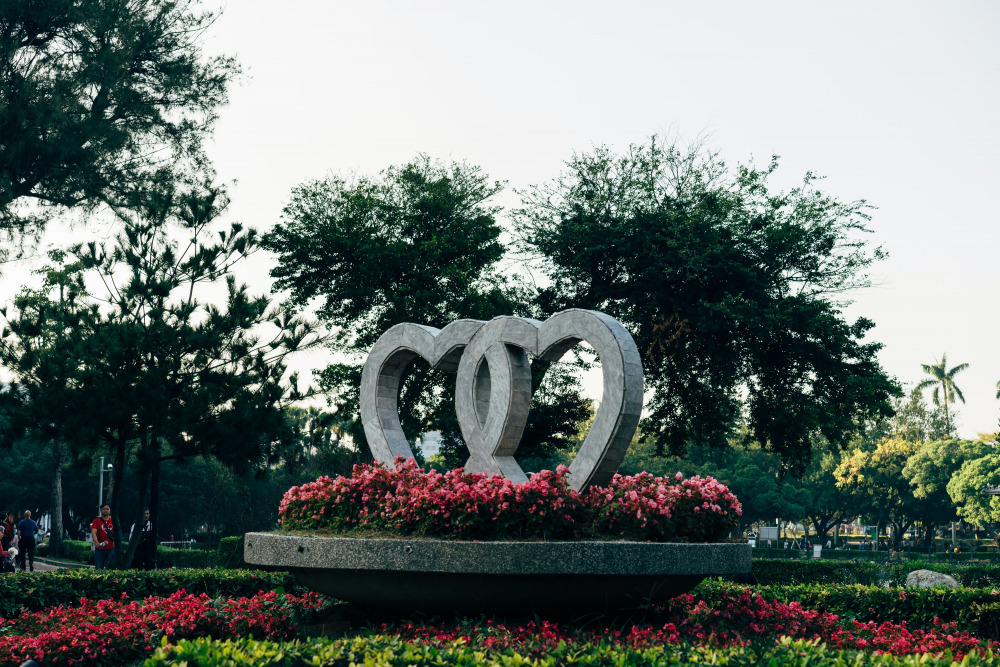 red flower and green bush plant with concrete heart fountain