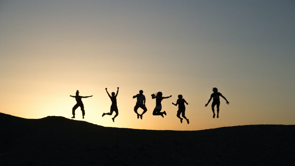 six silhouette of people jumping during sunrise